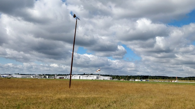 Long distance view of the Southampton Airport airfield, with grass in foreground and a wind vane