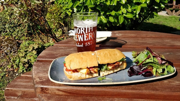 Pint of beer, panini and salad on a table in pub garden.