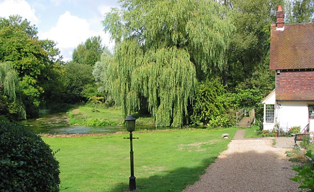 Itchen Way runs in front of the Fulling Mill and across the river. View of lawn, house, river and willow trees.