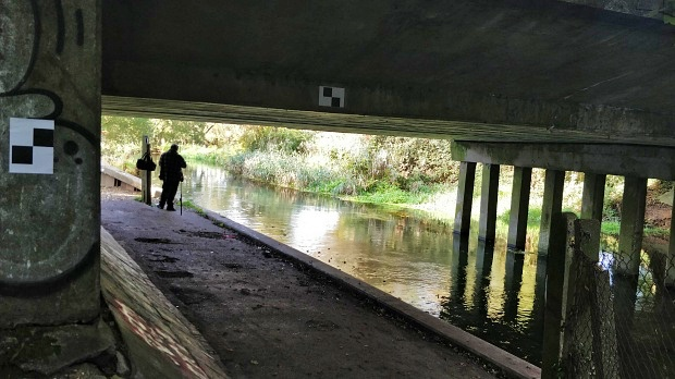 Concrete bridge carrying A34 over the River Itchen. A fisher stands on the bank.